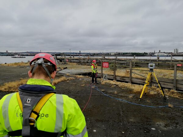 surveyors on old jetty structure with safety harnesses and ropes