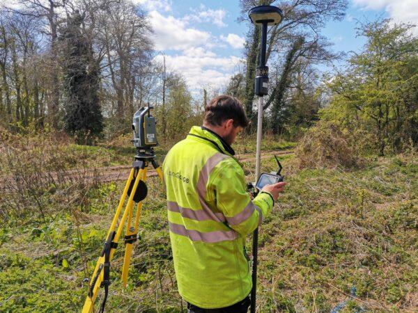 surveyor reading measurement on survey instrument in wooded area